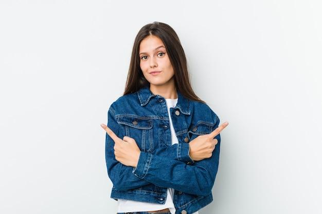 Jonge leuke vrouw wijst zijwaarts, probeert te kiezen tussen twee opties. Premium Foto