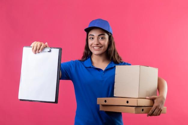 Jonge levering meisje in blauw uniform en pet houden pizzadozen en doos pakket met klembord kijken camera glimlachend vriendelijk staande over roze achtergrond Gratis Foto