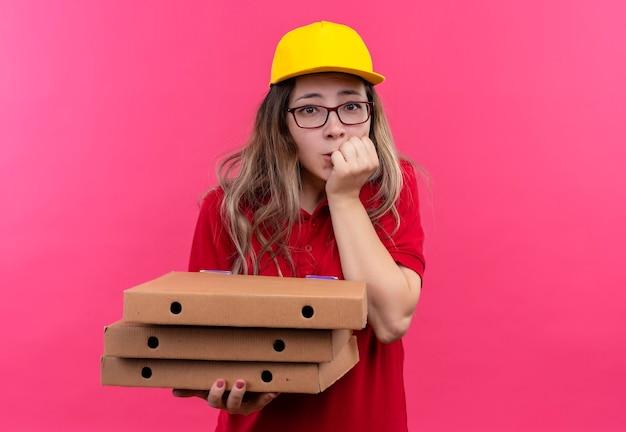 Jonge levering meisje in rood poloshirt en gele pet houden stapel pizzadozen bezorgd nagels bijten Gratis Foto