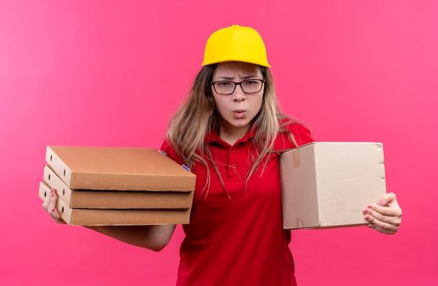 Jonge levering meisje in rood poloshirt en gele pet met stapel pizzadozen en doos pakket kijken naar cametra met fronsend gezicht Gratis Foto