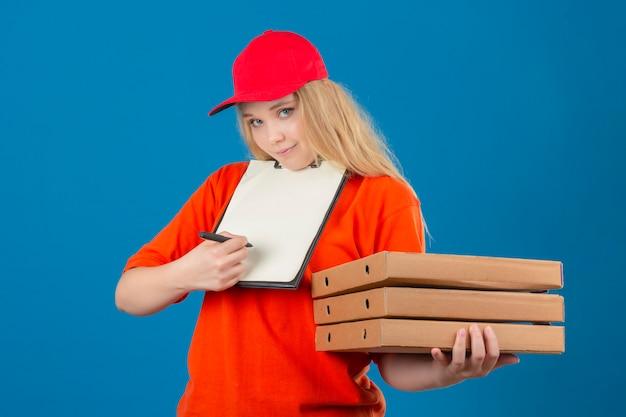 Jonge levering vrouw oranje poloshirt en rode pet dragen in medische beschermend masker staan met stapel pizzadozen en klembord met pen vragen om handtekening over geïsoleerde blauwe pagina Gratis Foto