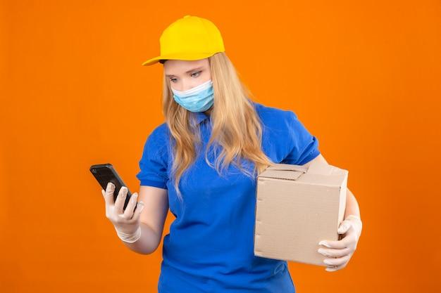 Jonge leveringsvrouw die blauw poloshirt en gele pet in medisch beschermend masker draagt ?? die zich met kartondoos bevindt die het scherm van haar smartphone bekijkt over geïsoleerde donkere gele achtergrond Gratis Foto