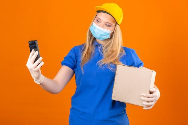 Jonge leveringsvrouw die blauwe poloshirt en gele pet in medisch beschermend masker draagt ?? die zich met kartondoos selfie op smartphone over geïsoleerde donkere gele achtergrond bevindt Gratis Foto