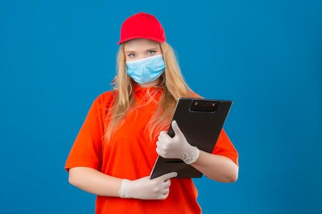 Jonge leveringsvrouw die oranje poloshirt en rode pet in medisch beschermend masker draagt ?? die zich met klembord in handen bevindt die camera met ernstig gezicht over geïsoleerde blauwe achtergrond bekijkt Gratis Foto