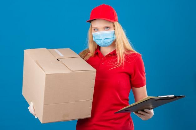 Jonge leveringsvrouw die rood poloshirt en pet in medisch beschermend masker draagt dat grote kartondoos en klembord houdt die camera met ernstig gezicht over geïsoleerde blauwe achtergrond bekijken Gratis Foto