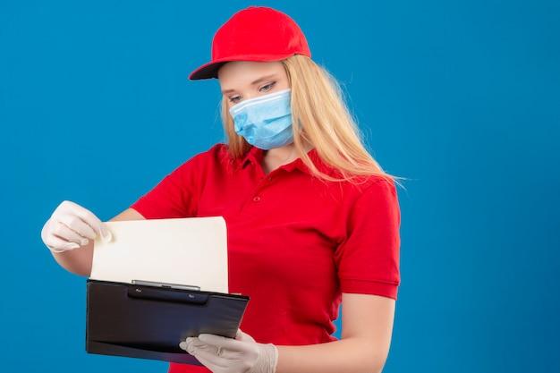 Jonge leveringsvrouw die rood poloshirt en pet in medisch beschermend masker draagt dat klembord in handen bekijkt met ernstig gezicht geconcentreerd op taak over geïsoleerde blauwe achtergrond Gratis Foto