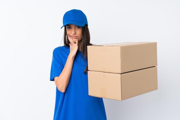 Jonge leveringsvrouw over geïsoleerde witte muur ongelukkig en gefrustreerd Premium Foto