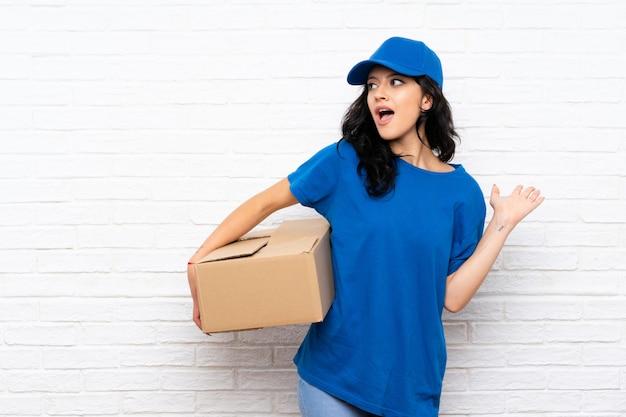 Jonge leveringsvrouw over witte bakstenen muur met verrassingsgelaatsuitdrukking Premium Foto