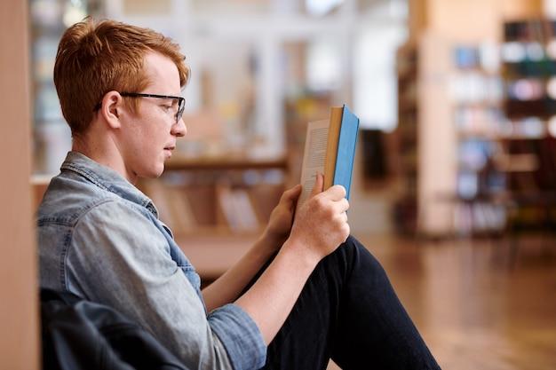 Jonge lezer in vrijetijdskleding door boekenplank in bibliotheek zitten tijdens het lezen van interessant boek Premium Foto