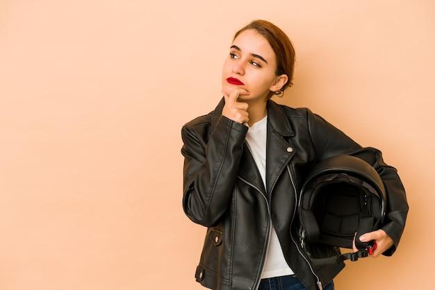 Jonge magere arabische tuinman vrouw opzij kijken met twijfelachtige en sceptische uitdrukking. Premium Foto