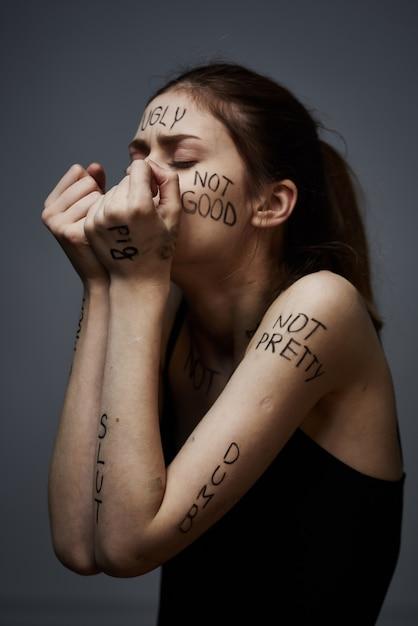 Jonge magere vrouw met beledigingen op het lichaam inscripties, slechte woorden, depressieve toestand, eenzaamheid Premium Foto