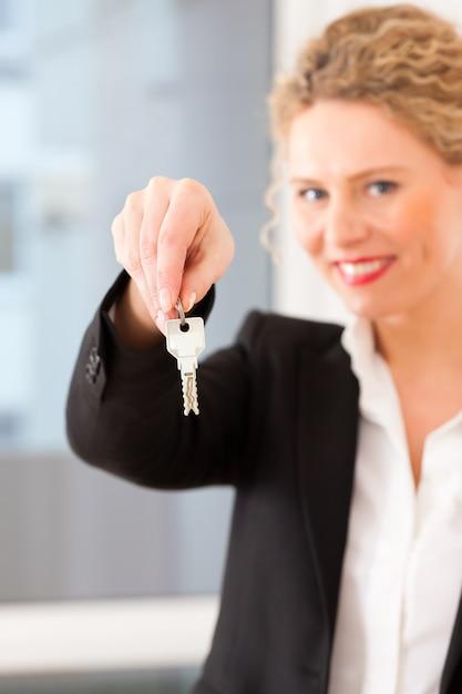 Jonge makelaar is met sleutels in een appartement Premium Foto