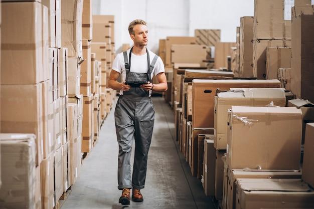 Jonge man aan het werk in een magazijn met dozen Gratis Foto