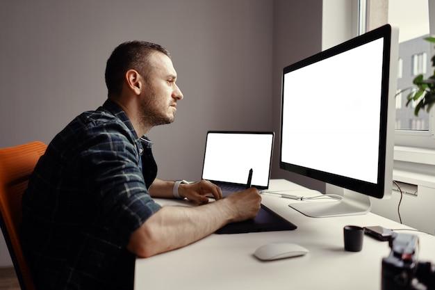 Jonge man aan het werk met interactieve pendisplay en computer Gratis Foto