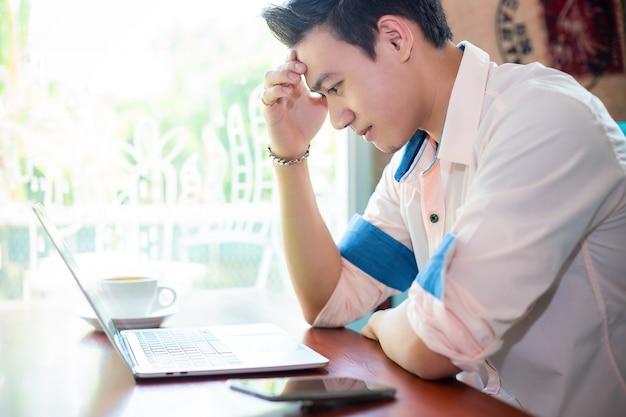 Jonge man aan het werk met laptop in café Gratis Foto