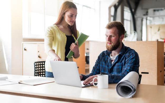 Jonge man aan het werk op laptop met collega's op balie in kantoor Gratis Foto