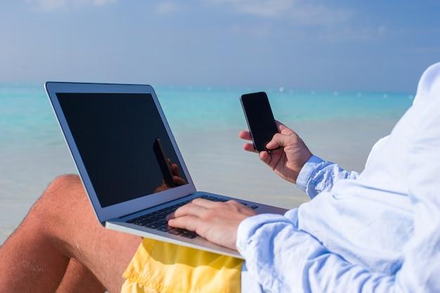 Jonge man aan het werk op laptop op tropisch strand Premium Foto