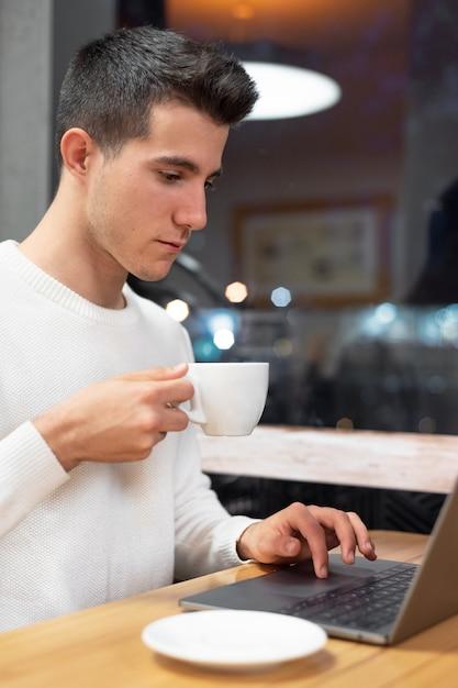 Jonge man aan het werk op zijn laptop in een koffieshop, jonge student te typen op de computer. Premium Foto