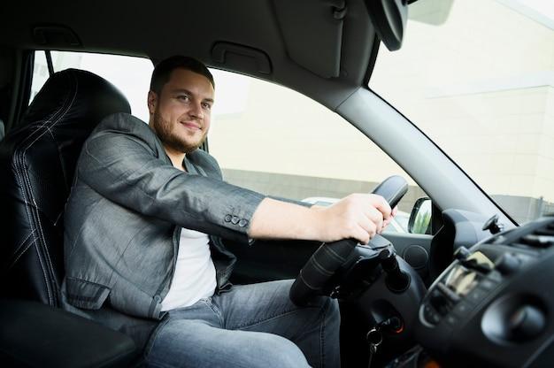 Jonge man achter het stuur kijken naar de camera Gratis Foto