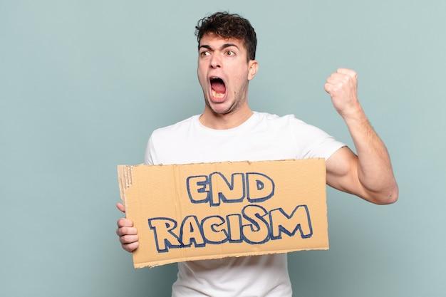 Jonge man agressief schreeuwen met een boze uitdrukking of met gebalde vuisten het vieren van succes Premium Foto