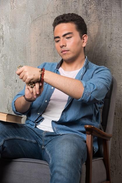 Jonge man armband zetten en zittend op een stoel met boek over marmeren achtergrond. hoge kwaliteit foto Gratis Foto