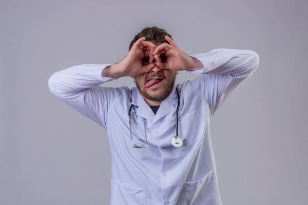 Jonge man arts witte jas dragen en stethoscoop die ok gebaar zoals verrekijkers doen die tong uit plakken, kijkend door vingers, gekke uitdrukking Gratis Foto