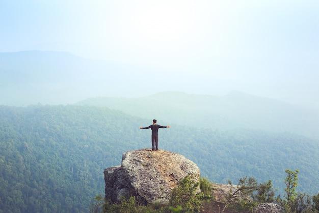 Jonge man azië toeristische op berg waakt over de mistige en mistige ochtend zonsopgang Premium Foto