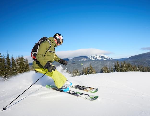 Jonge man backpacker skiën op en neer hellingen. mannelijke skiër opleiding in zonnige winterdag. backcountry skiën concept. Premium Foto