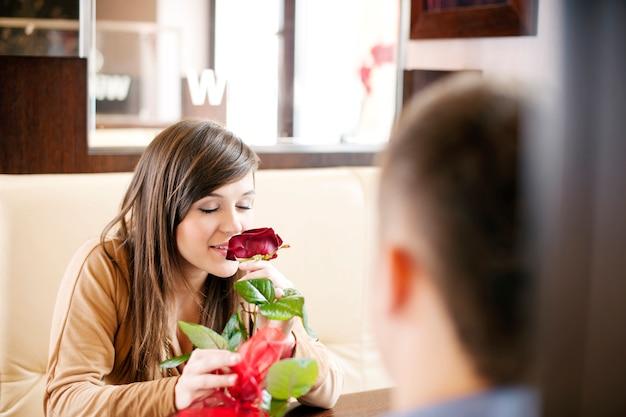 Jonge man die een roos zijn vriendin geeft Gratis Foto