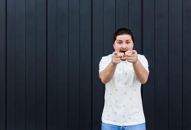 Jonge man die en vingers schreeuwen tonen tegen camera tegen zwarte achtergrond Gratis Foto