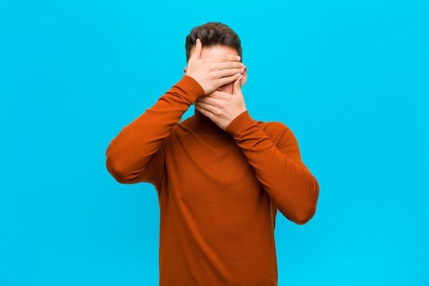 Jonge man die gezicht bedekt met beide handen nee zeggen tegen de camera! afbeeldingen weigeren of foto's over de blauwe muur verbieden Premium Foto