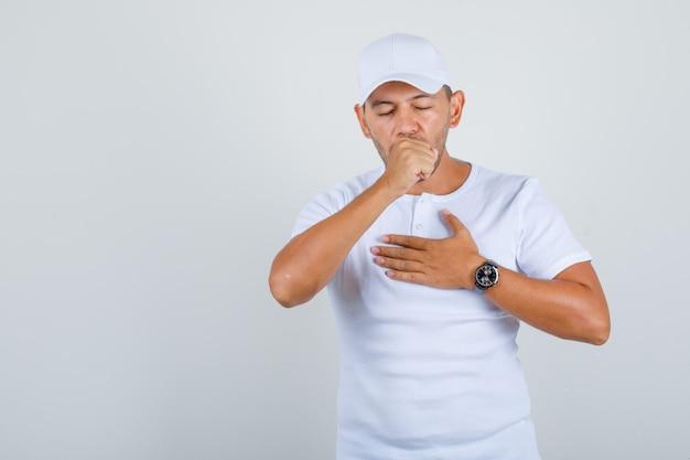 Jonge man die lijdt aan hoest in wit t-shirt, pet en ziek, vooraanzicht kijkt. Gratis Foto