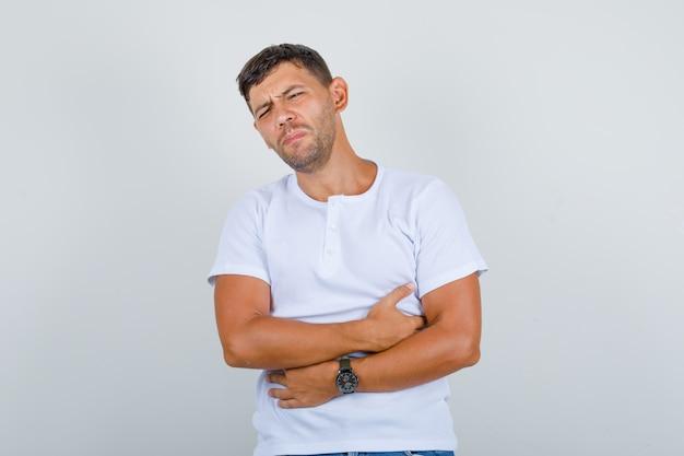 Jonge man die lijdt aan maagpijn in wit t-shirt en ziek, vooraanzicht kijkt Gratis Foto