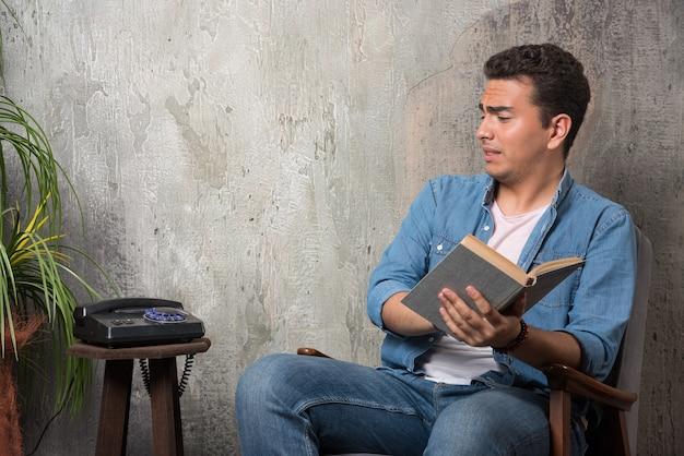 Jonge man die met boek op telefoon kijkt en op stoel op marmeren achtergrond zit. hoge kwaliteit foto Gratis Foto