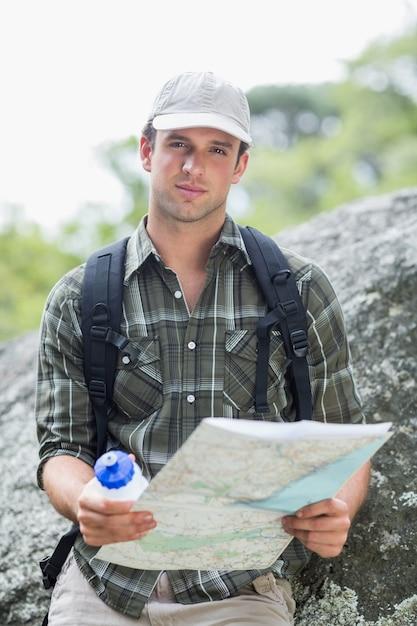Jonge man die met fles en kaart Premium Foto