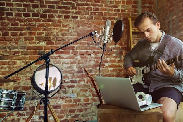 Jonge man die muziekvideo blog thuisles opneemt, gitaar speelt of uitzending internet tutorial maakt terwijl hij op de zolder werkplek of thuis zit Gratis Foto