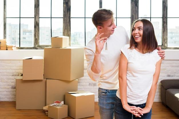 Jonge man die sleutels toont aan zijn gelukkige vrouw Gratis Foto