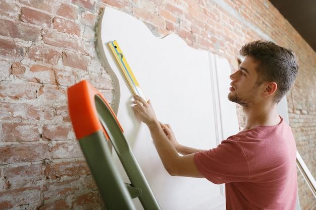 Jonge man die voor het doen van appartementreparatie door hisselfes voorbereidingen treft. voor het opknappen of renoveren van het huis. concept van relaties, familie, diy. het opmeten van de muur voordat u gaat schilderen of ontwerpen. Gratis Foto