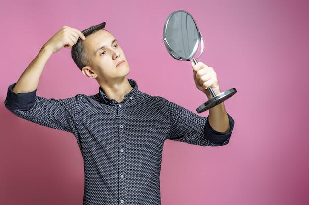 Jonge man die zijn haar voor een spiegel op een roze achtergrond kamt. Premium Foto