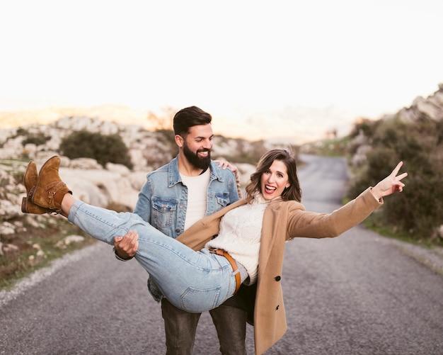Jonge man die zijn mooie vriendin vervoert Gratis Foto