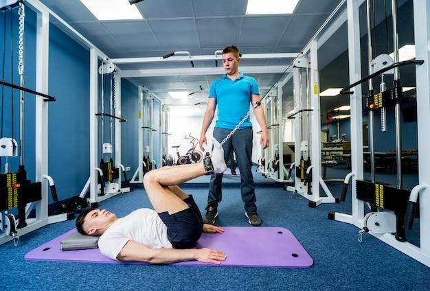 Jonge man doen oefeningen op mat onder toezicht van fysiotherapeut. Premium Foto