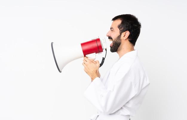 Jonge man doet karate schreeuwen door een megafoon Premium Foto