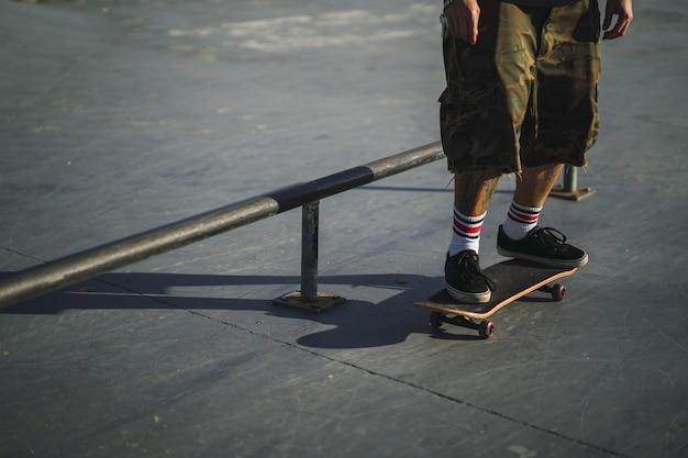 Jonge man doet verschillende trucs met een skateboard in het park Gratis Foto