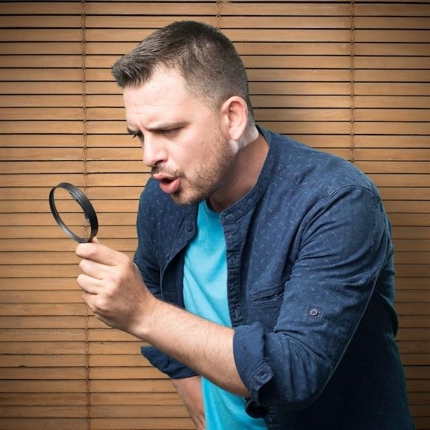 Jonge man draagt een blauwe outfit. met behulp van een vergrootglas. Gratis Foto