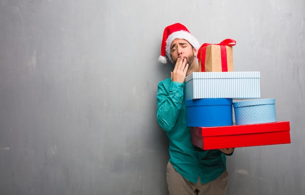 Kerstmuts Met Licht : Jonge man draagt een kerstmuts met geschenken moe en erg