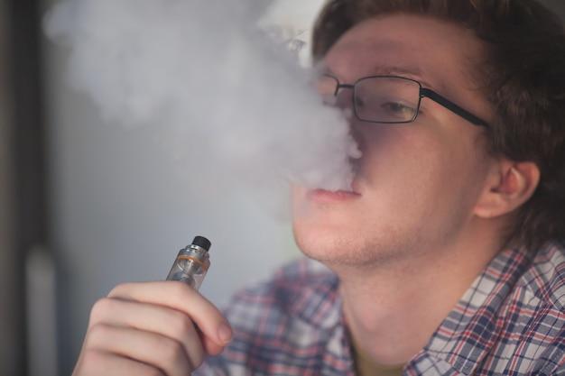 Jonge man elektronische sigaret roken. Premium Foto