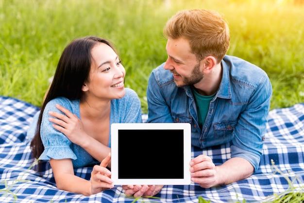 Jonge man en aziatische vrouw die elkaar bekijken en tablet tonen Gratis Foto
