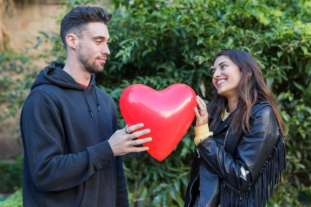 Jonge man en lachende vrouw met ballon in vorm van hart Gratis Foto