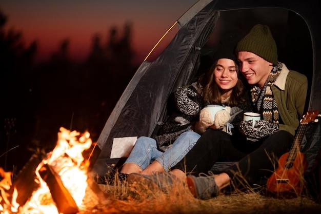Jonge man en vrouw die van een vuur genieten Gratis Foto