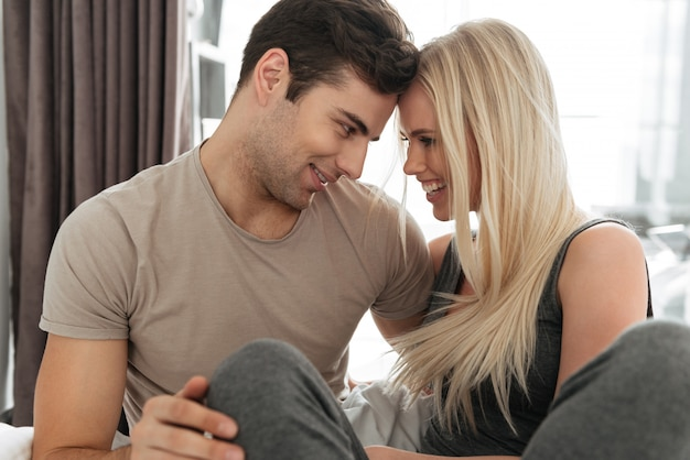 Jonge man en vrouw flirten en knuffelen in bed Gratis Foto